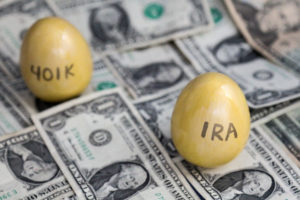 "Golden eggs with ""401K"" and ""IRA"" written on them, on top a pile of dollar bills"