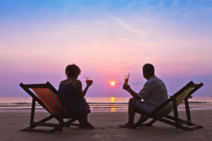Couple on the beach, drinks in hand, watching the sun set