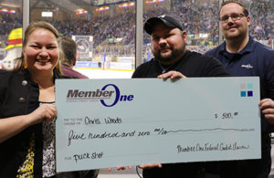Member One staff presenting check to puck shot contest winner
