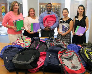 Member One staff presenting school supplies to Lucy Addison Middle School