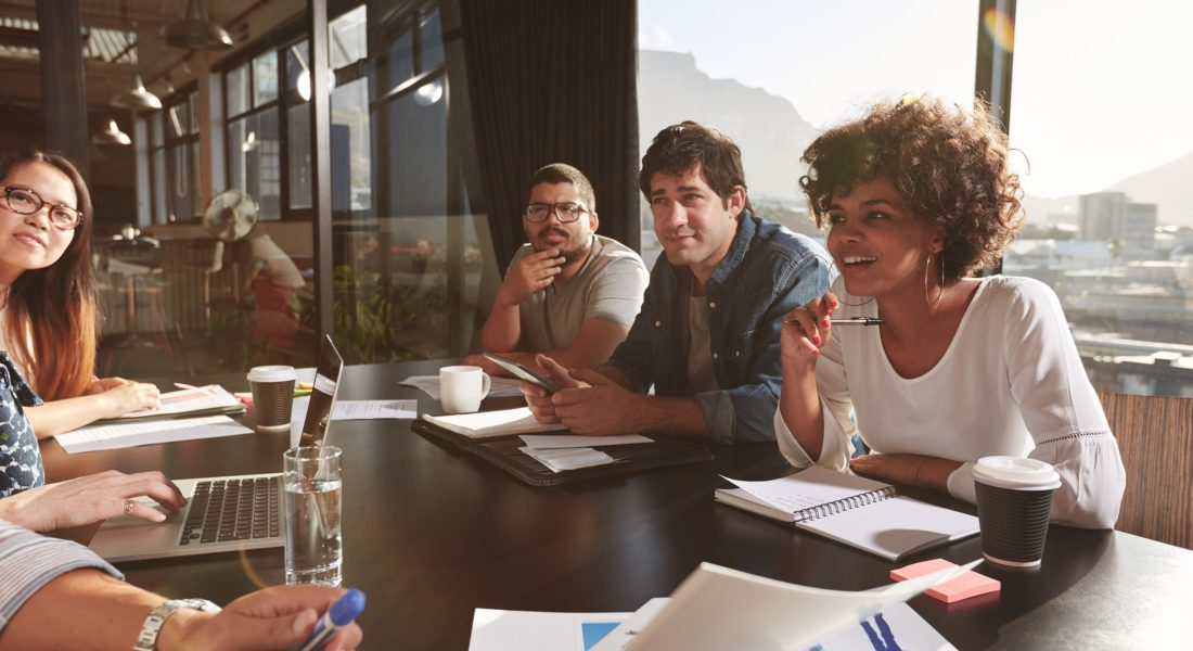Young professionals, informal meeting around a table with a city view