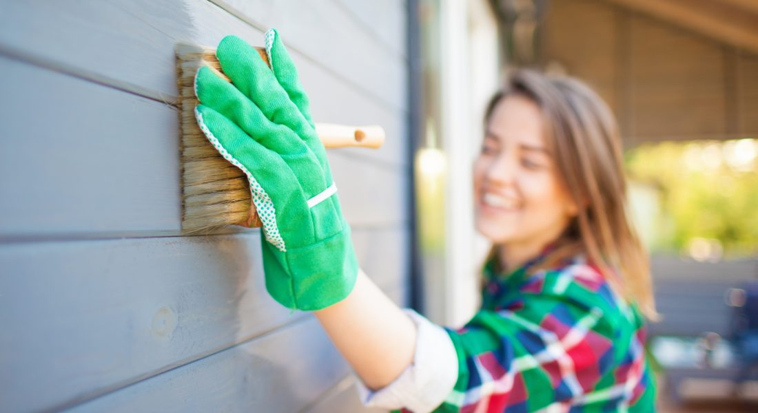 Woman cleaning siding, home improvement project