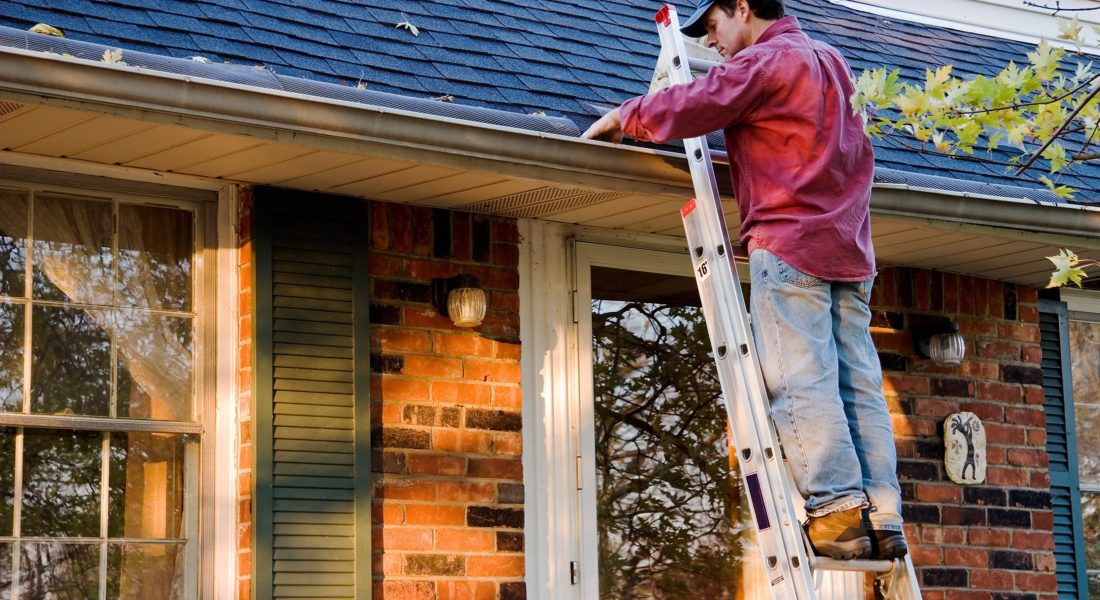 Man on ladder cleaning gutters on home.​