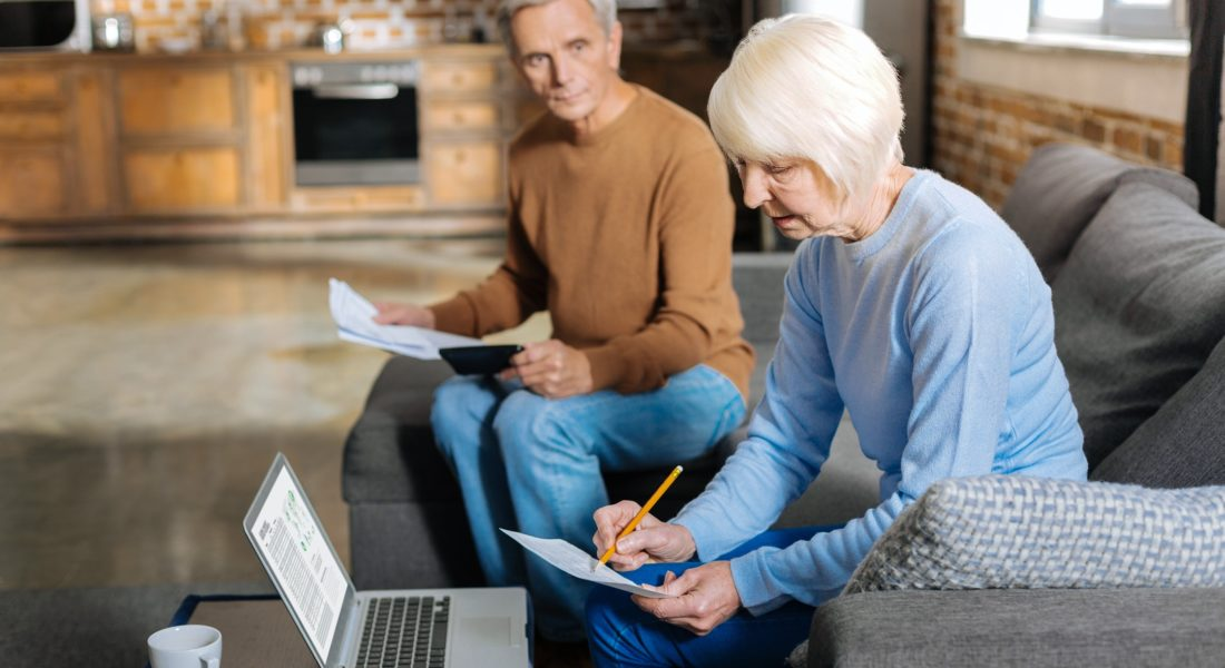 Older couple reviewing document in front of a computer together