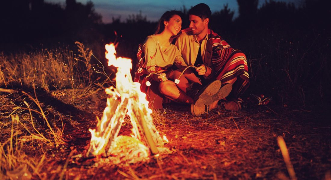 Couple sitting by a campfire