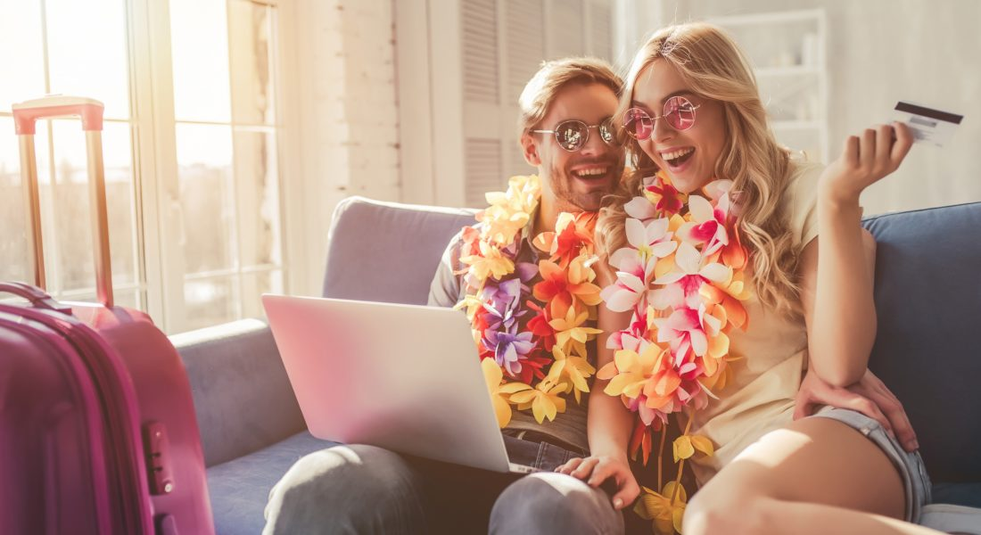 Couple on a couch with a laptop while wearing leis and holding a credit card