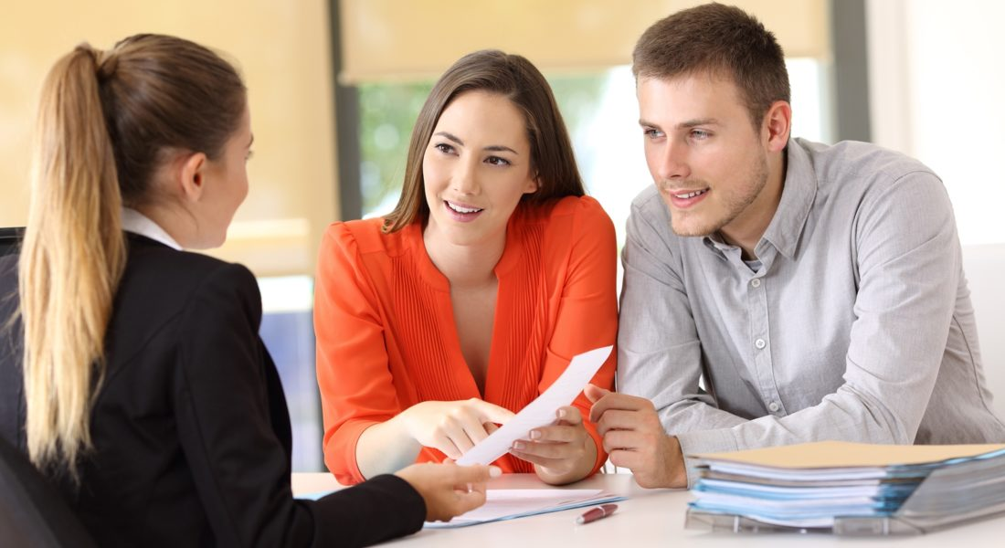 Couple reviewing paperwork with a financial professional