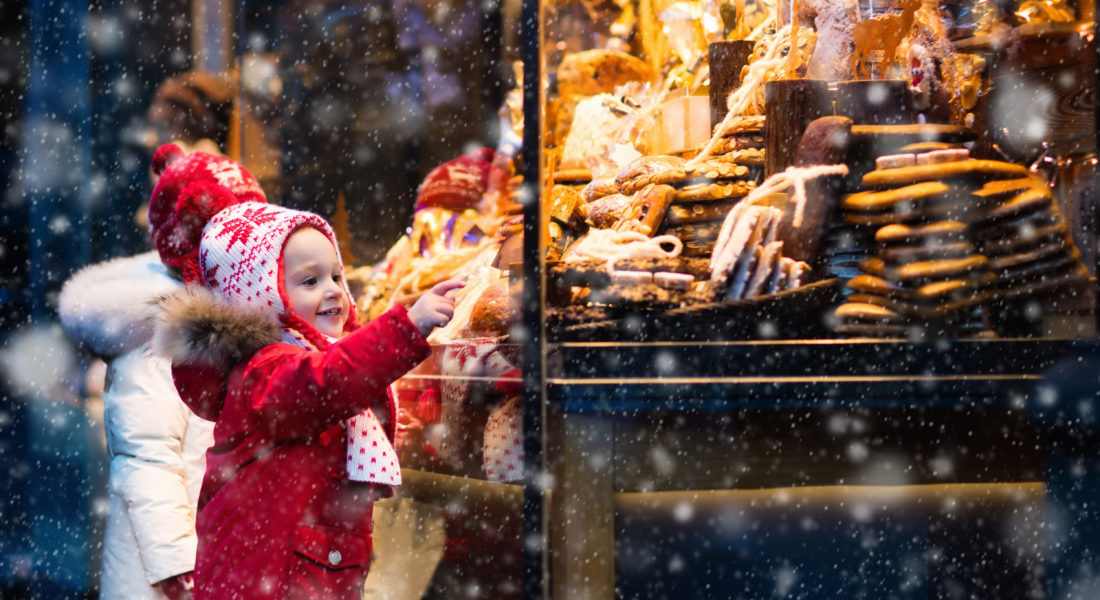 Young children bundled up, looking at holiday display in storefront window