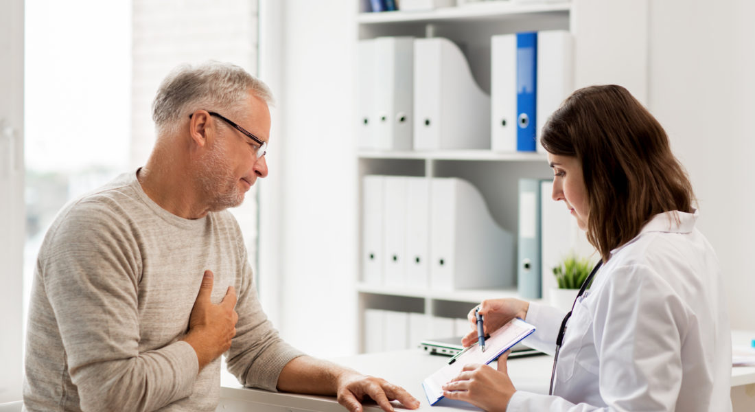 Middle-age man reviewing medical documents with doctor