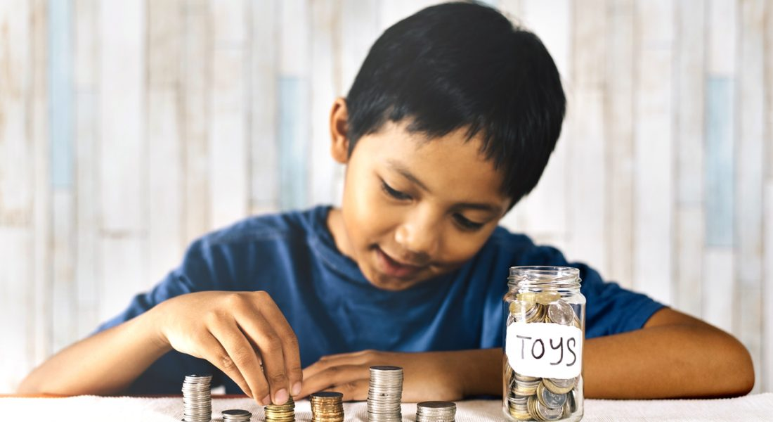 "Child counting coins and placing them in a jar labeled ""toys"""