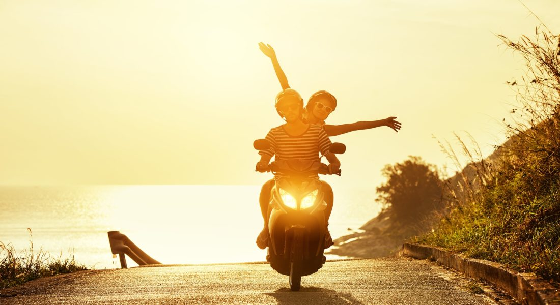 Couple Riding Motorcycle On The Beach At Sunrise