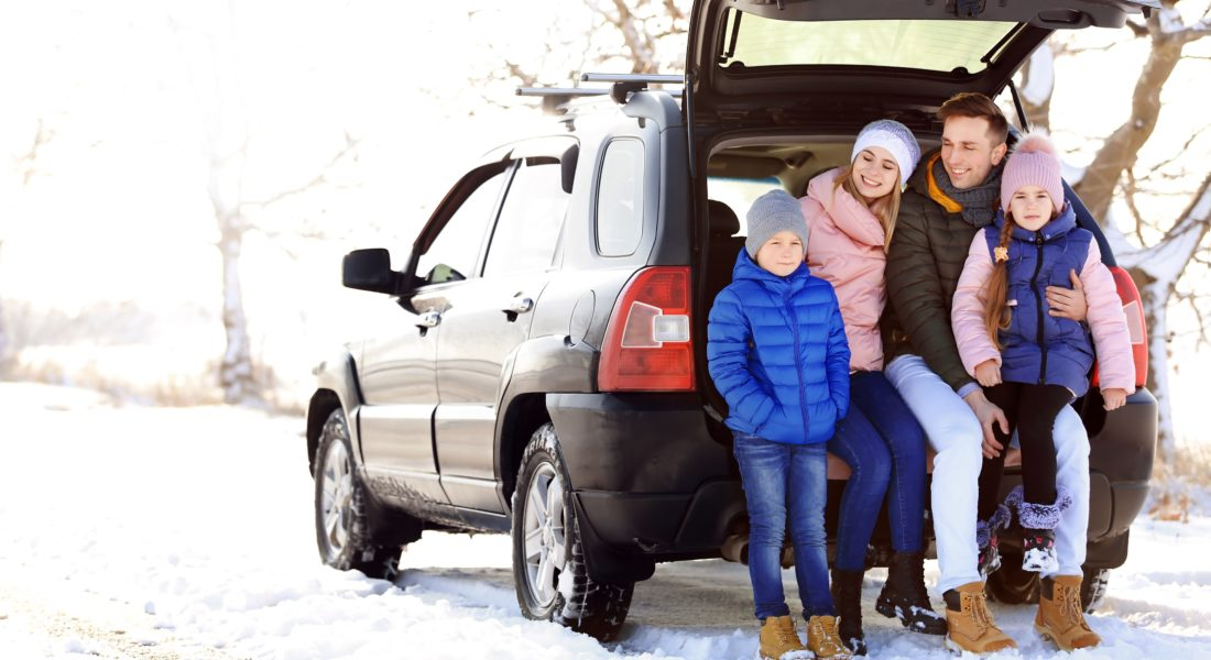 Family In Winter Jackets Sitting In Car