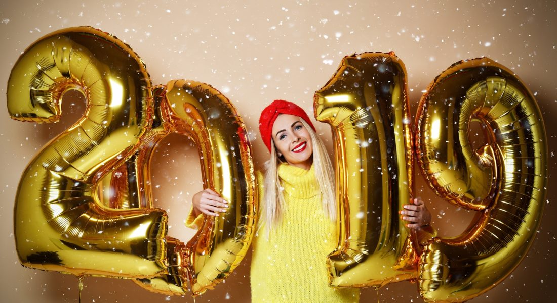 Woman Smiling And Holding Gold Inflated 2019 Balloons