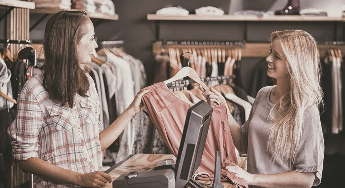 Young Woman At Clothing Store Checkout Hands Shirt To Sales Associate