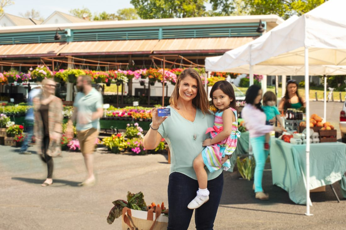 Member Everyday Credit Card. Woman at Farmers market, holding daughter and credit card and smiling at camera