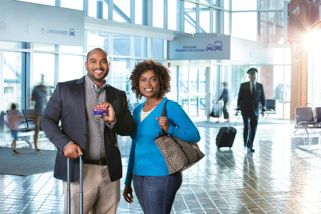 Man and woman stand in airport smiling at camera and holding premier credit card.
