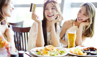 Group of women having lunch and paying with credit cards