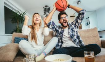 Couple watching basketball game on the sofa at home.