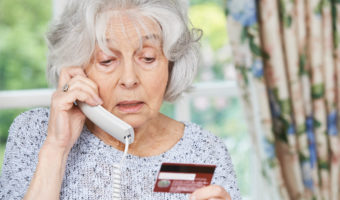Elderly woman on the phone holding a credit card