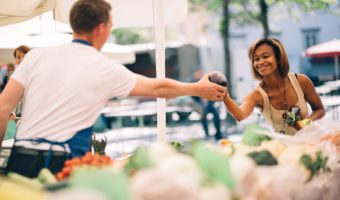 Young woman buying vegetables at farmers market.