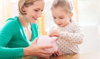 Mother holding piggy bank while young daughter places a coin inside