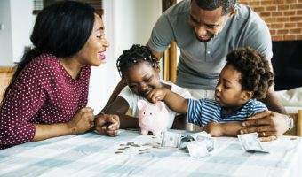 Parents help children count money in piggy bank.