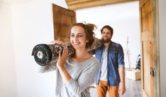 Young married couple moving in new house, carrying a carpet together.