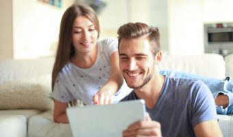 Smiling Young Couple Sit Together In Living Room Woman Points To Tablet In Mans Hands