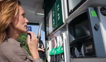 Woman With Credit Card In Hand Hesitates At Gas Pump