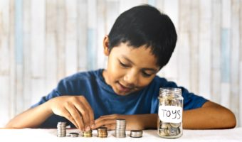 """Child counting coins and placing them in a jar labeled """"toys"""""""