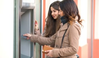 Two Young Women Withdraw Cash From Atm