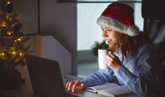 Woman Wearing Santa Hat Searches For Jobs On Her Laptop