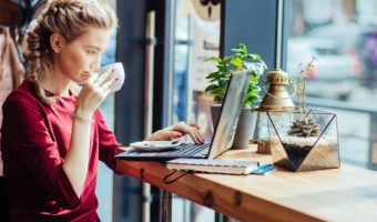 Young Woman Sips Coffee And Views Laptop In Cafe